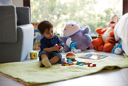 Toddler On A Mat Playing With Toys
