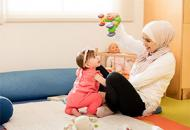 Mother Holding A Toy Playing With Her Toddler