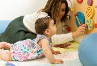 Mother And Baby Girl Playing Together On An Interactive Board