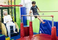 Boy Playing On Gymnastic Bars While His Mother Watches