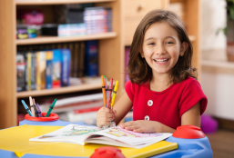 A Girl Sitting On A Desk With Coloring Book And Crayons